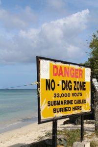 Warnschild an der Cable Bay auf Tobago in Trinidad und Tobago in der Karibik. Hier kommt eine Versorgungsleitung mit Strom an Land an. Das Schild warnt davor das Kabel zu zerstören oder beschädigen.
